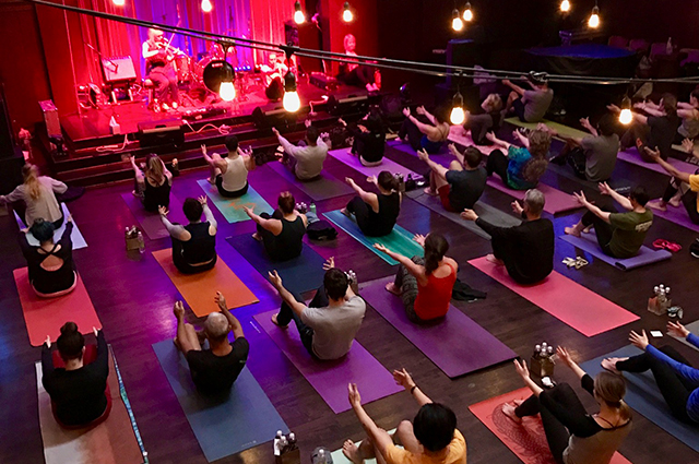 A large group of people sitting on yoga mats and doing poses in front of a large stage with a musician performing