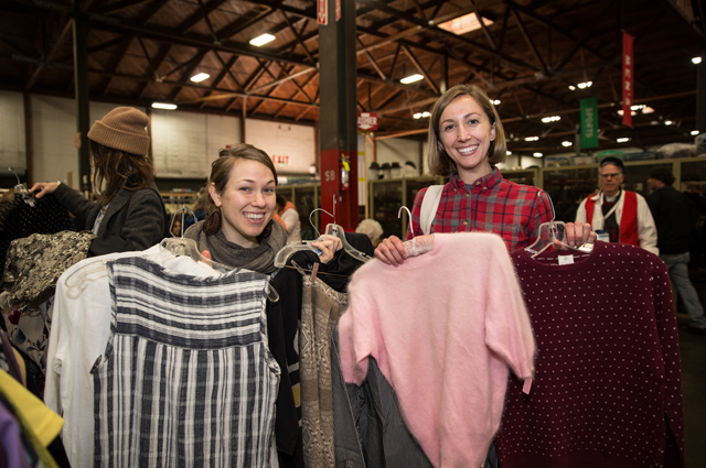 Two women holding up shirts and sweaters they found at the White Elephant Sale