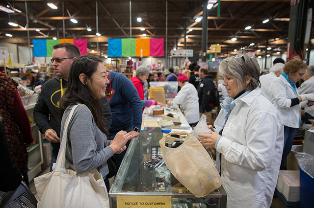 A woman buys an item at the White Elephant Sale