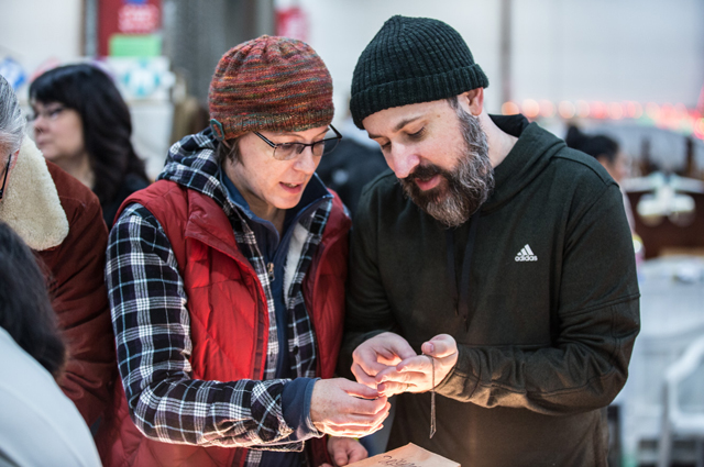 A man and woman look at jewelry in the White Elephant Sale