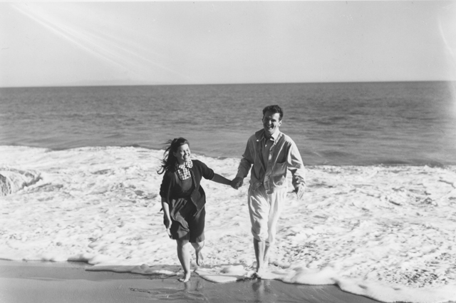 A black and white image of Charles and Ray Eames smiling at the beach