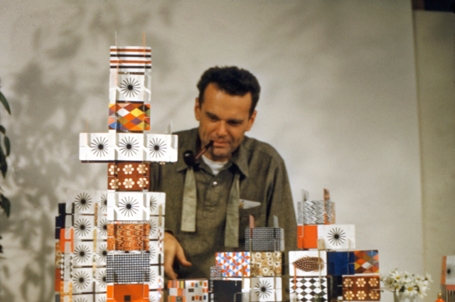 Charles Eames sitting at a table with a house of cards
