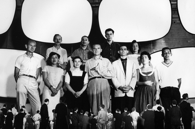 A black and white photo of the Eames staff standing side by side