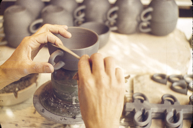 Edith Heath's hands carving a clay mug with other finished mugs in the background