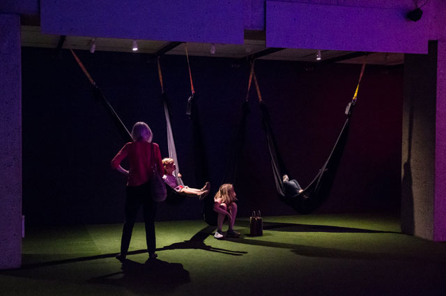 Museum visitors enjoying hammocks and swings inside Nature's Gift: Humans, Friends, and the Unknown at Oakland Museum of California