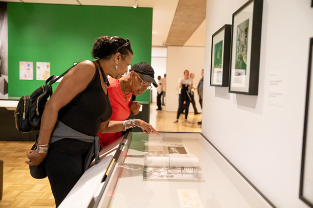 Two women pointing at a display case in The World of Charles and Ray Eames