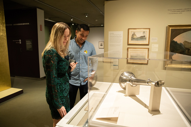 Two people view a horn in a glass case in the art gallery