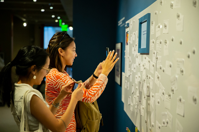 Two women take photos with their phones of notecards hung on a blue wall