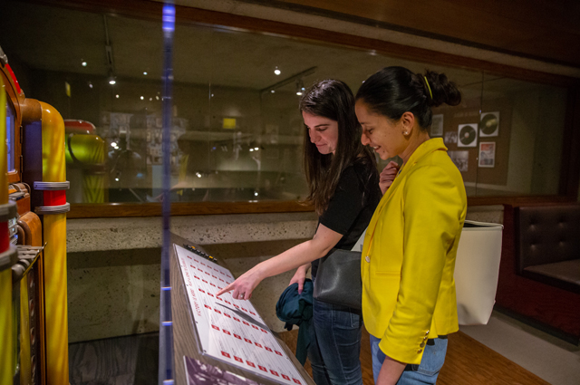 Two women read the song choices for a jukebox