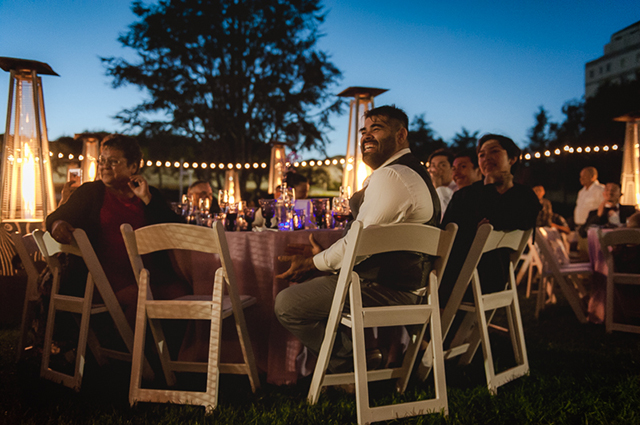 A man smiling and sitting at a large wedding table in the OMCA Gardens