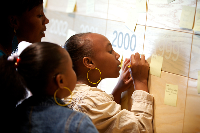 A mother and two daughters add a note to a long wooden timeline at the year 2000