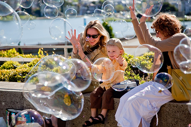 Two woman and a small child sit in the OMCA Gardens surrounded by bubbles