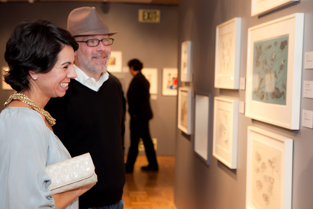 Woman and man smile as they look at artwork