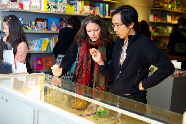 Two people look into a jewelry case in the OMCA store