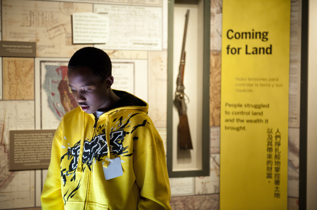 "A young boy in a yellow hoodie reads information in a section of the gallery called ""Coming for Land"""