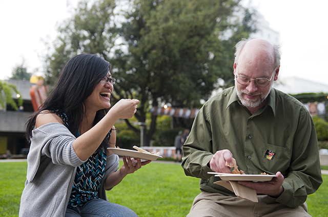 Two people talk and laugh as they eat food in the OMCA Gardens