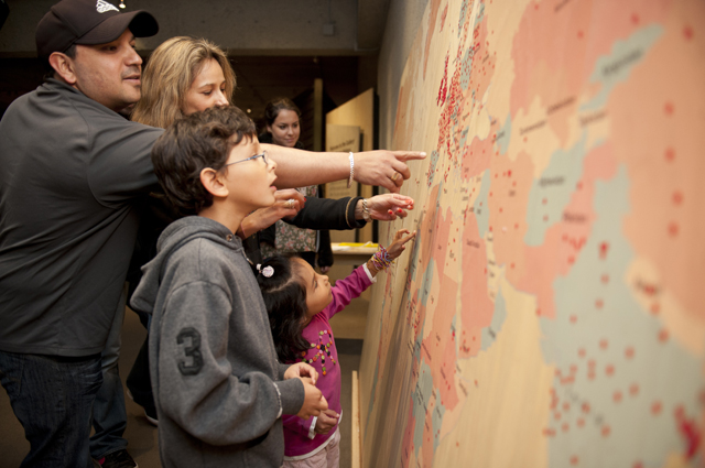 A family points at a large multicolored map of the world with tiny dots sprinkled across it