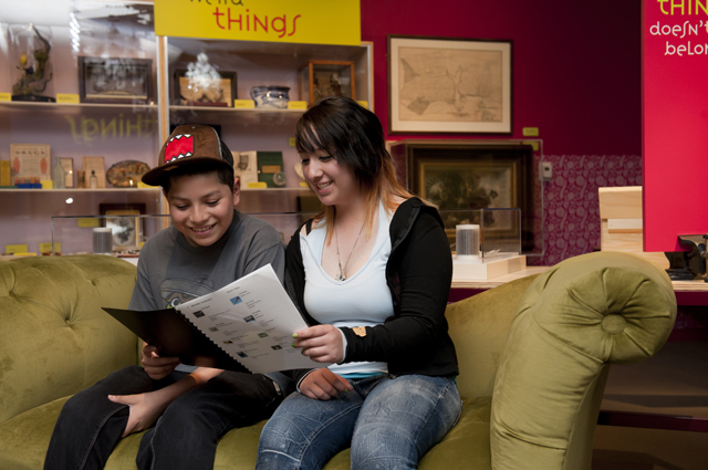 Two people read a booklet in the history gallery
