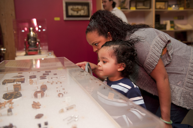 A mother and her young son view tiny objects in a glass case