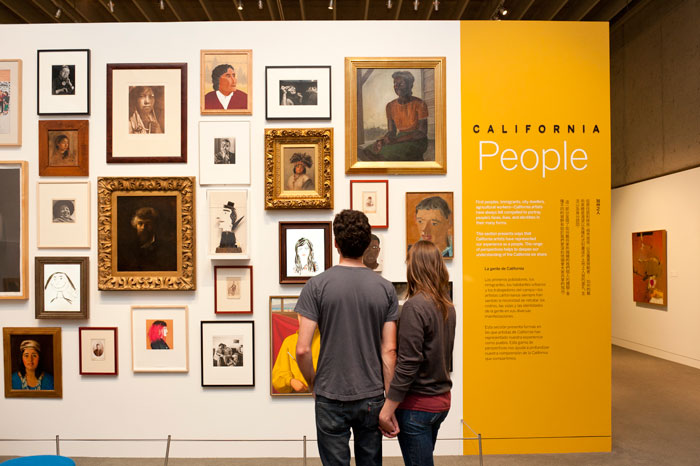 People looking at portraits inside the art section of OMCA in Oakland