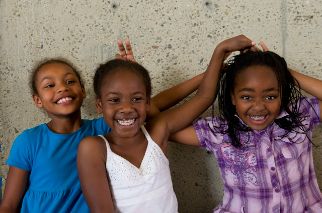 Children pose smiling in front of a concrete wall at the Oakland Museum of California