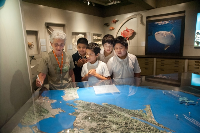 A woman with a group of four young boys looking at a large 3D map