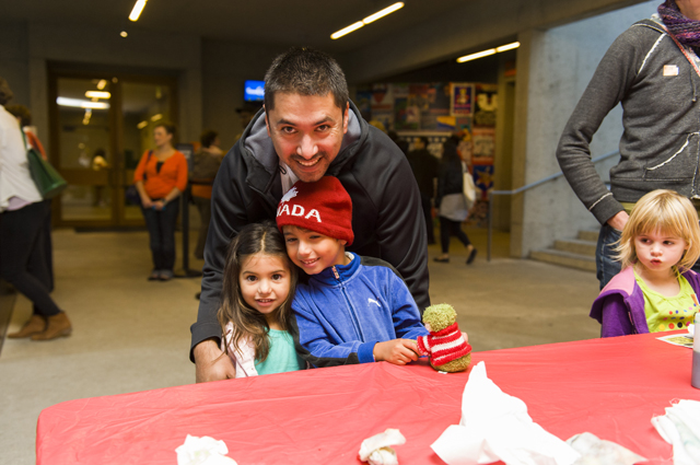 A father hugs two children as they smile at the camera at OMCA