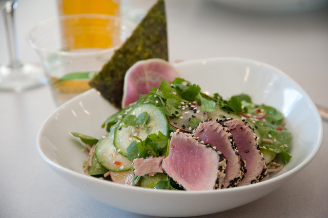 An ahi tuna salad in a white bowl on a white table
