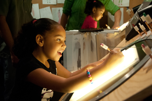 A girl smiles as she draws on a lit up screen