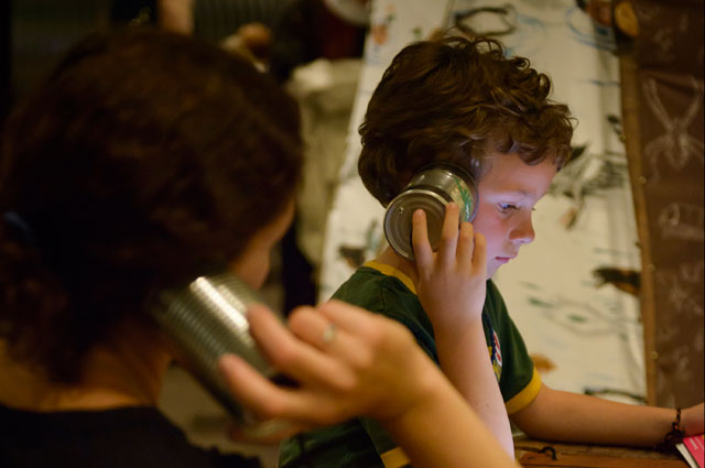 A young child listening to an interactive exhibit at the Oakland Museum of California