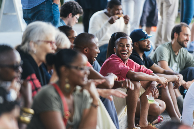 A man sitting on the steps of the amphitheater laughing amongst friends