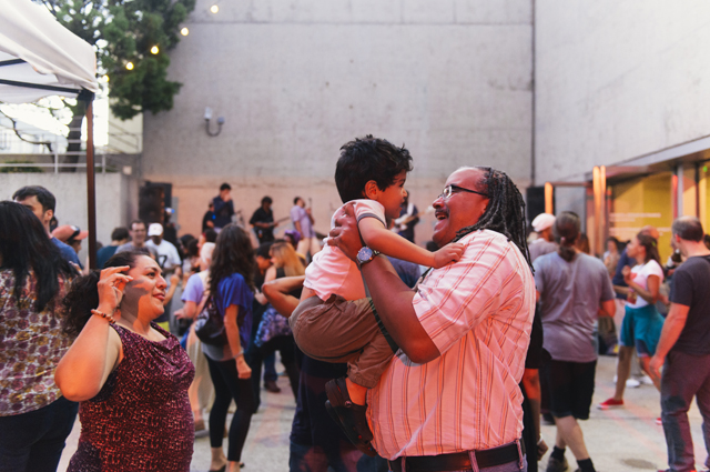 A man holds up a smiling young boy as people dance in the background