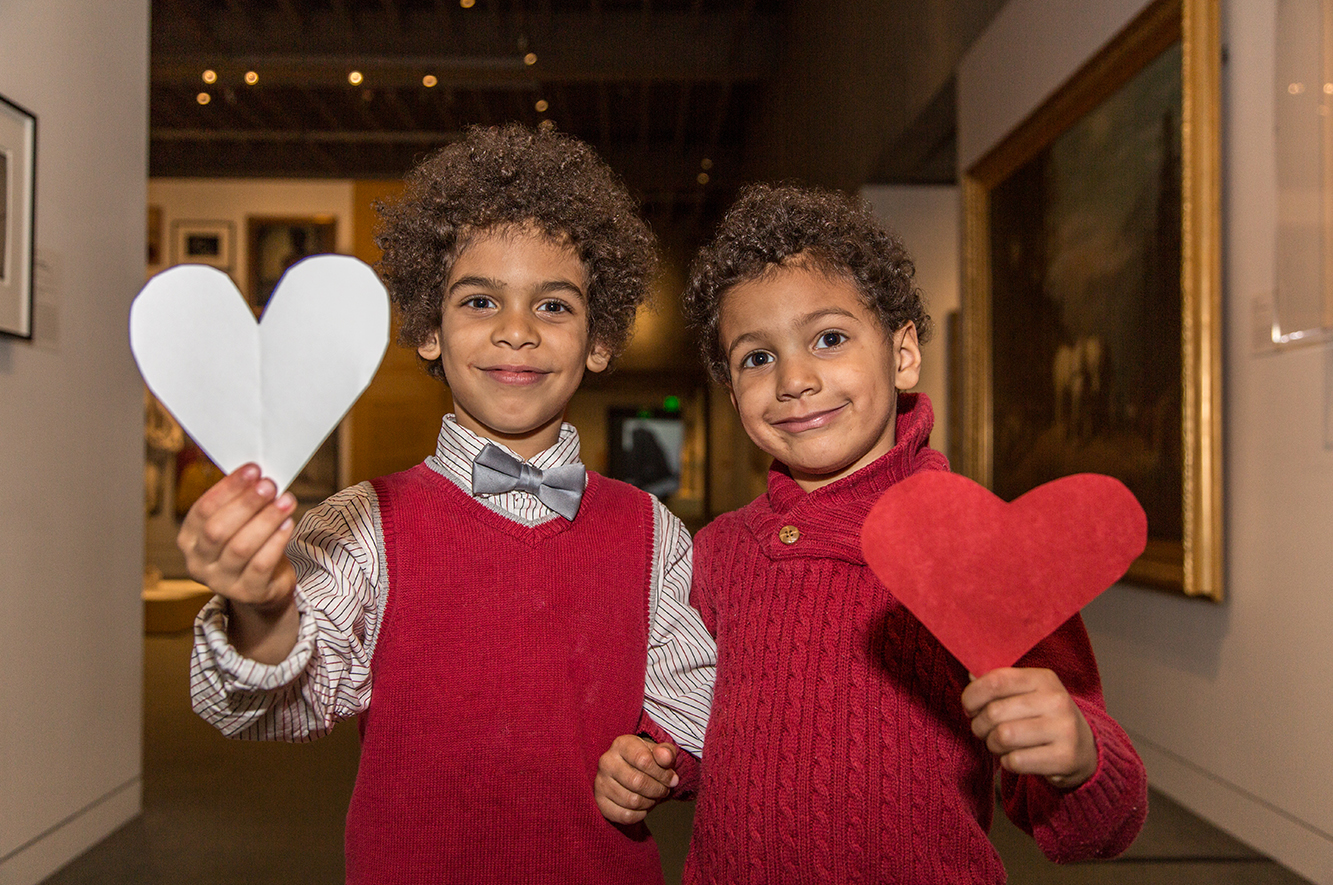 Two young twin boys hold paper hearts inside OMCA's Gallery of California Art