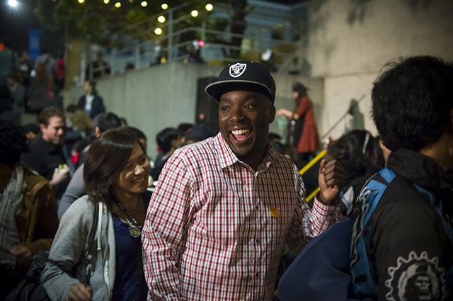 A man smiles and dances among a crowd at Friday Nights at OMCA