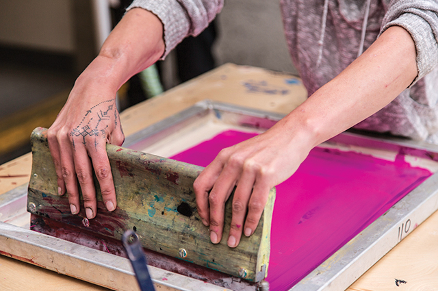 Close up on a woman's hands as she screenprints a pink sheet