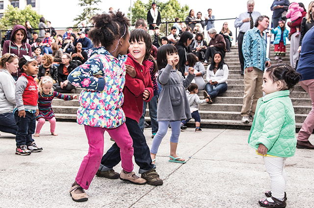 A group of children smile and dance together in the 10th street amphitheater at OMCA