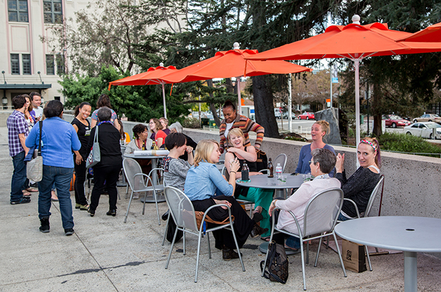 A large group of people sitting and laughing on the terraces outside at Blue Oak cafe