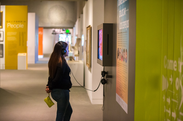 A woman watches a video in the art gallery with headphones on