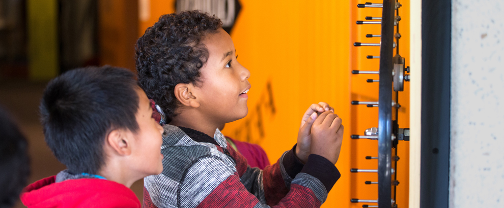 Two young children play with an interactive wheel of fortune at the Oakland Museum of California
