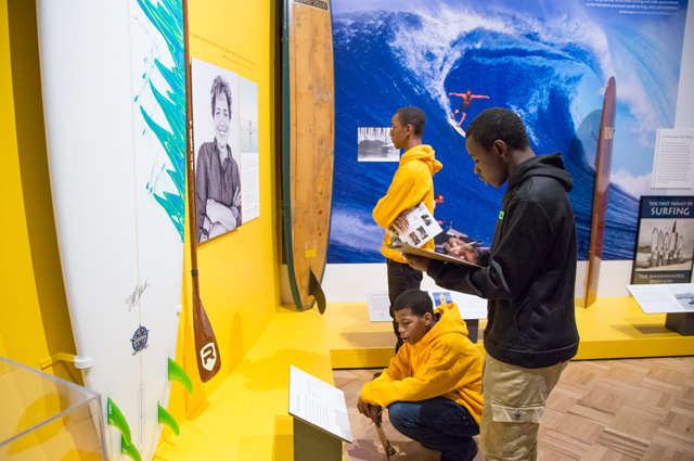 Teenagers in a museum exhibit about surfing