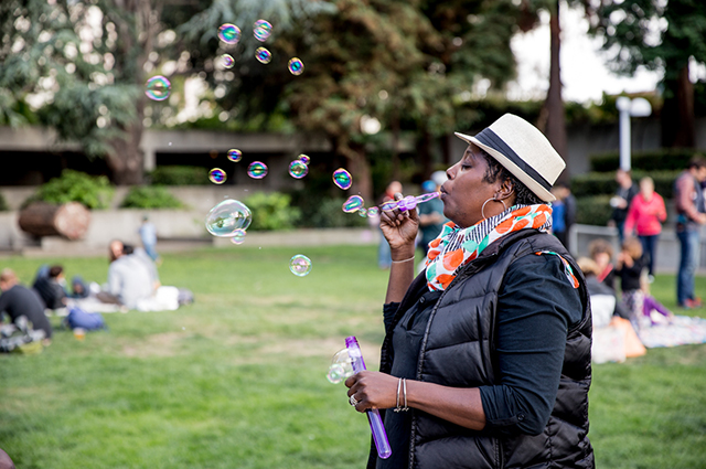 A woman blows bubbles in the OMCA Gardens
