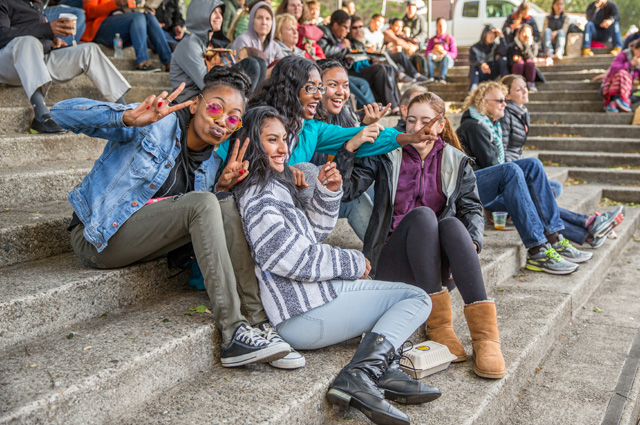 youth laughing and sitting on the steps of OMCA