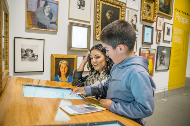 A mother and son interact with a touch screen with paintings in the background