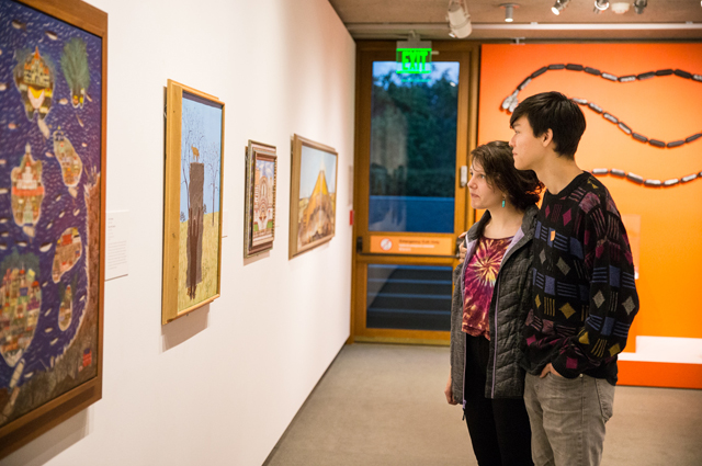 Two people look at a row of paintings in the art gallery