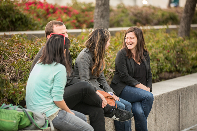 Four teachers sit in the OMCA gardens talking and laughing