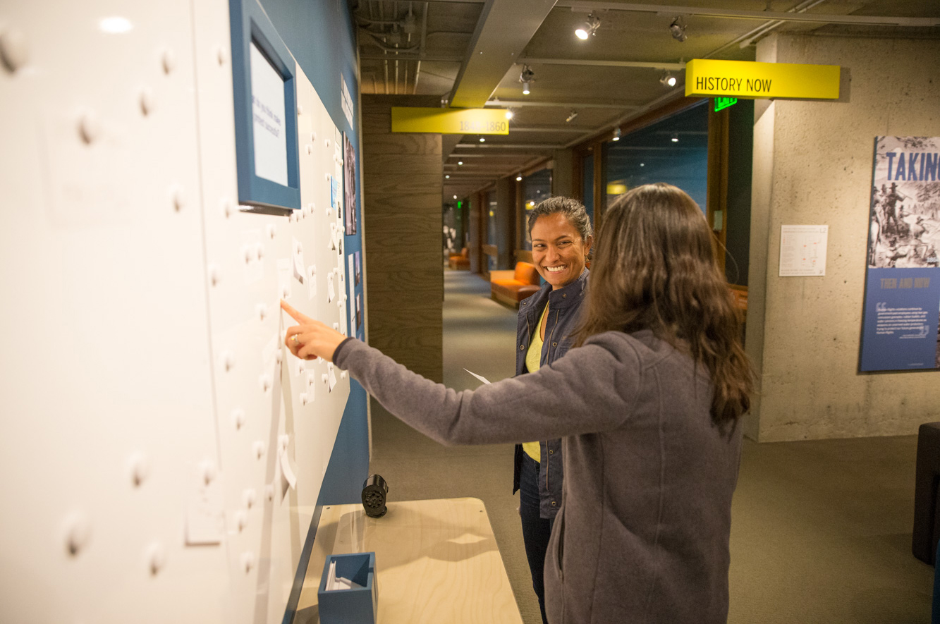 Two women smile as they look through OMCA's Gallery of California History