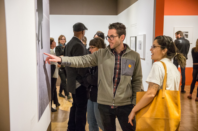 A man and woman point and chat about artwork inside of a crowded art gallery