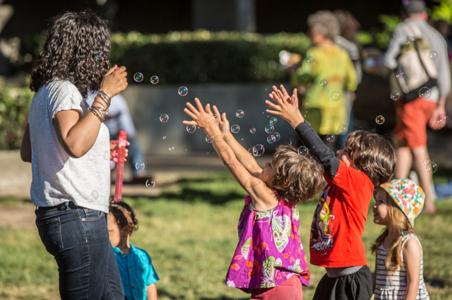 A woman blows bubbles while children raise their hands trying to catch them