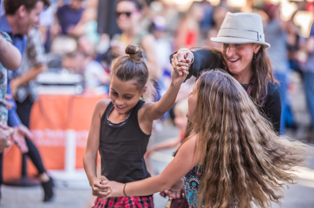 A woman twirls two girls around on the dance from at Friday Nights at OMCA