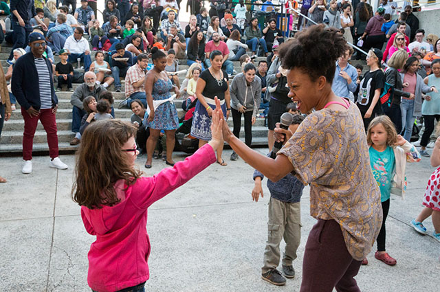A woman with a microphone high fives a young girl in the crowded OMCA amphiteater